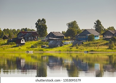 Country landscape: old wooden house on the lake with boats. Reflections of a building in the water on a bright summer day