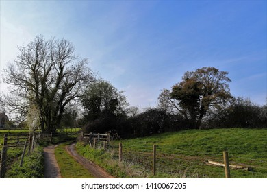 Country lane landscape in early spring near Syresham village, South Northamptonshire, England with clear blue sky, bare trees and glimpse of church behind.