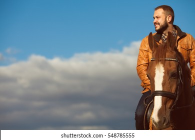 Country life concept. Young relaxed and smiling rich man in light brown leather jacket riding a horse. Sunny cloudy weather. Wide open spaces. Copy-space. Retro style. Outdoor shot