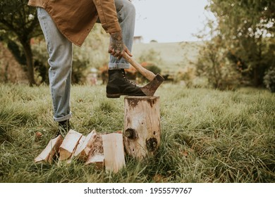 Country man splitting wood with axe on the field