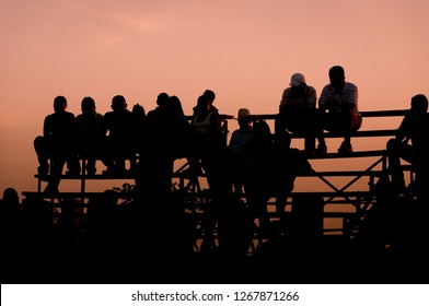 Country men sitting on rodeo seats at sunset