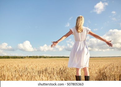 country, nature, summer holidays, vacation and people concept - happy young woman in white dress on cereal field