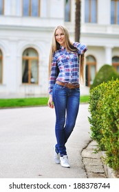 the country portrait of the young beautiful girl in a plaid shirt and jeans smiles