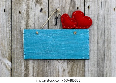 Country red fabric hearts and black iron house key hanging on antique teal blue blank rustic wooden sign; Valentine's Day background with painted wood copy space
