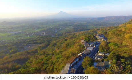 country road around the hills with valley panoramic and a mountain. Transportation infrastructure in Asia and Indonesia with aerial drone camera