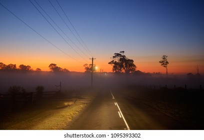 Country road in Australia illuminated by headlamps, beautiful sunset in background.