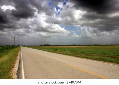 a country road with clouds above