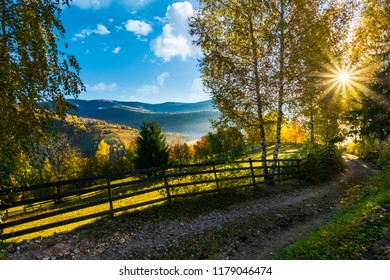 country road down the hill in to the sunrise. beautiful rural landscape in autumn. wooden fence along the road