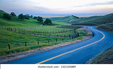 COUNTRY ROAD IN EARLY EVENING AMONGST FARM PASTURES NEAR BAKERSFIELD, CALIFORNIA