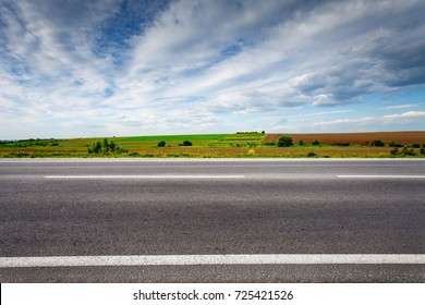Country road with field on horizon. Side view. Rural landscape in summer day