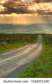 Country Road going into the distance with Crepuscular rays in the sky, Pennines, Cumbria, England,  United Kingdom