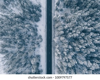 Country road going through the beautiful snow covered landscapes. Aerial view. Drone photography