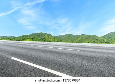 Country road and green mountains natural landscape under the blue sky