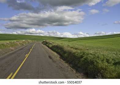Country road with green rolling hills and big clouds.