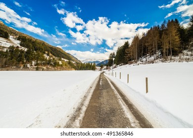 country road leading through a winter mountain landscape.