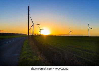 Country road leading to wind turbines in a field in the UK at sunset or sunrise against a clear winter sky