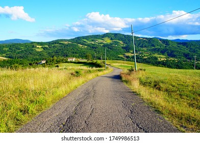 Country road in the middle of the picture and mountain landscape on the background.