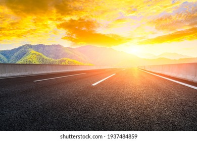 Country road and mountain in summer at sunset.