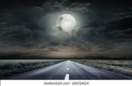 country road at night with large moon