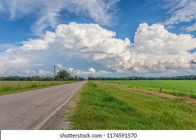Country road in Oklahoma with white clouds against a blue sky.