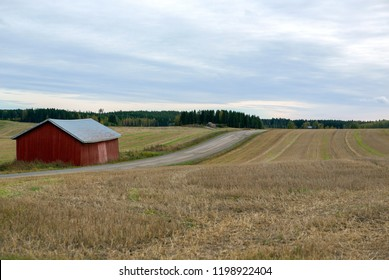 Country road on a cloudy day. Gravel road in the country side, old red barn.