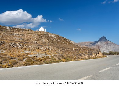 Country road on the island of Crete with small church and mountain