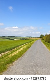 a country road overlooking english agricultural scenery under a blue summer sky in the yorkshire wolds