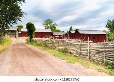 Country road with roundpole fences on the sides. Village barns in the background. Location Stensjo in Smaland, Sweden.