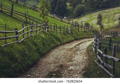 Country road and rustic wooden fences in a traditional Transylvanian village, Brasov county, Romania. Back on track.