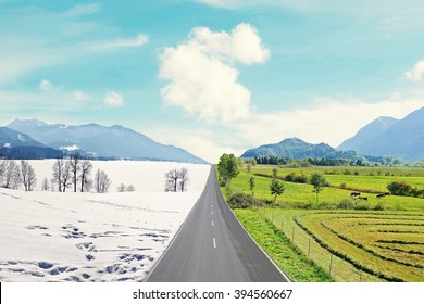 country road through mountainous winter and spring landscape, seasons rotation, climate change