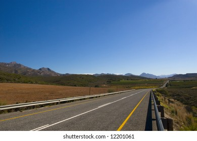 A country road through the mountains on a clear day with blue sky
