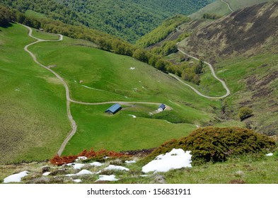 A country road is twisting on the green pasture between the glacis forested and steep slope covered with snow in the spring mountains Pyrenees.