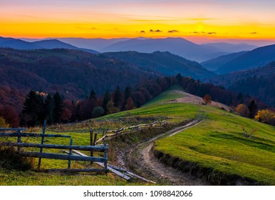 country road winding down the hill at dusk. forested mountain ridge in the distance. lovely scenery of Synevyr National park area, Ukraine