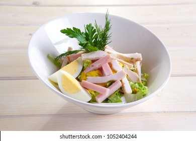 Country salad with egg, ham, chicken fillet and vegetables