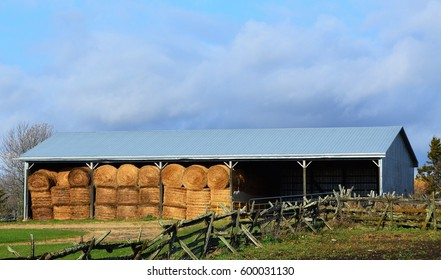 Country shed with round hay bales in modern storage shed.