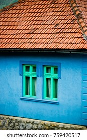 country side house vivid bright blue color wall with two green windows and roof, country side house