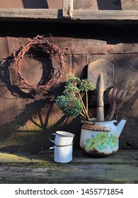 Country still life with vintage housewares and vintage garden tools against the rusty metal wall. Aged wooden background. Sunny day. Sunlight and shadows