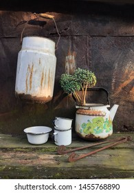Country still life with vintage rusty houseware ( can, kettle, mug, bowl ) against the rusty wall. Aged wooden table top