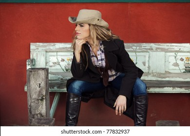Country style fashion portrait of a beautiful long-haired blond young woman wearing a cowboy hat and sitting on an old bench in front of a red wall. Shallow depth of field.