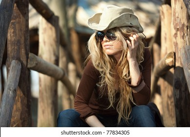 Country style fashion portrait of a beautiful long-haired blond young woman wearing a cowboy hat and sunglasses. Shallow depth of field.