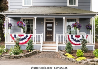 Country Style Home with Red, White and Blue Patriotic Banners and Hanging Baskets of Flowers on the Porch