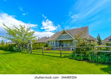 Country style house with nicely trimmed front yard, lawn wide long  in a residential neighborhood. Vancouver, Canada.