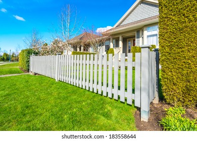 Country style long wooden fence with nicely trimmed grass.