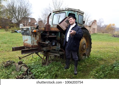 Country style man with retro radio broadcast receiver on shoulder stands happy smiling outdoor on old half disassembled tractor background - peasant lifestyle