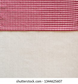 Country Style Red and White Checked Cloth Napkin along side of Off White Linen Tablecloth as blank Background with room or space for your copy, text or design.  Square crop photo from above view