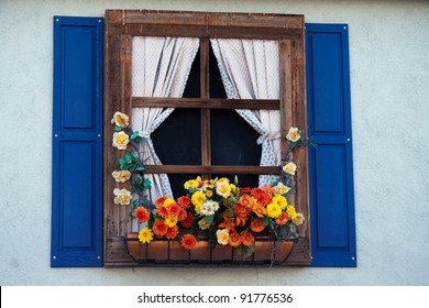 Country style window with flowers,planter, shutters and curtains