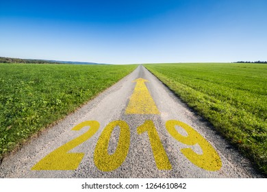 country trail or gravel road with the word 2019 and an yellow arrow showing forward to the horizon, business concept for turn of the year