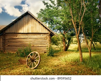 country yard with trees, wheel and plow