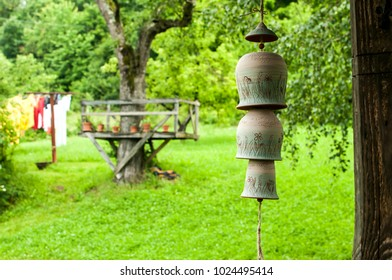 Countryhouse garden view with ceramic clay pottery decorative garden wind chime bells on a rope in front