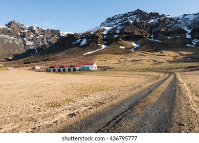 Countryroad leading to a typical Icelandic farmhouse under the mountains covered in snow in Iceland